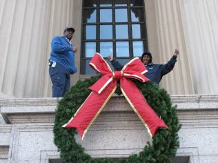 LB&B employees hanging the wreath over door to Archives 1, 2013