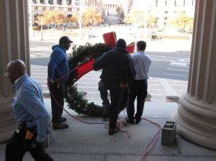 LB&B employees hanging wreath over door to Archives 1, 2013