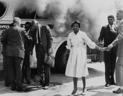 Freedom Rider Mae Frances Moultrie Howard stands by a burning Greyhound bus in Anniston, Ala. on May 14, 1961.